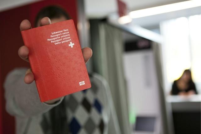 Un homme tient son nouveau passeport Suisse biometrique au nouveau centre de biometrie au Flon, ce vendredi 21 janvier 2011 a Lausanne. Ce centre va recolter les donnees biometriques pour les passeports suisse ainsi que pour les cartes de sejour biometrique. A partir du 24 janvier 2011, les titres de sejour biometriques pour les ressortissants etrangers des Etats tiers deviennent obligatoires. (KEYSTONE/Anthony Anex)
